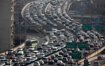 A general view of heavy traffic on a highway during the morning rush hours in Shanghai March 26, 2012. China may be the world's No. 2 oil consumer and have the world's biggest vehicle market but current high oil prices are unlikely to dent growth in fuel demand much or sales of fuel-guzzling sports utility vehicles. The country, which imports 56 percent of the oil it needs, is set to lead global oil demand again this year by contributing nearly half of the world's incremental fuel use, although the pace has slowed. Pictures taken March 26, 2012. REUTERS/Carlos Barria (CHINA - Tags: TRANSPORT ENERGY BUSINESS) - RTR2ZYED