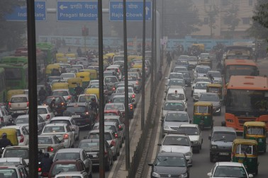 Vehicles sit in traffic on a road shrouded in haze in New Delhi, India, on Monday, Jan. 20, 2014. India, China and Brazil, three of the largest developing nations, joined the U.S. in a list of the biggest historical contributors to global warming, according to a study by researchers in Canada. Photographer: Kuni Takahashi/Bloomberg